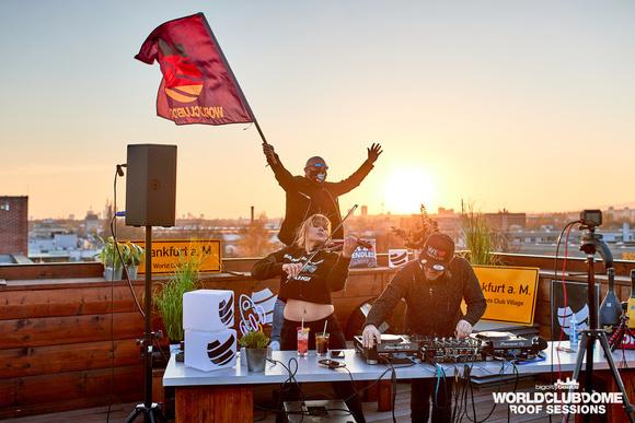 DJ, Violinistin, Mann mit Fahne, Skyline, Rooftop