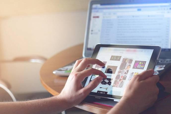 Mensch benutzt Tablet, Laptop im Hintergrund, Onlinesuche