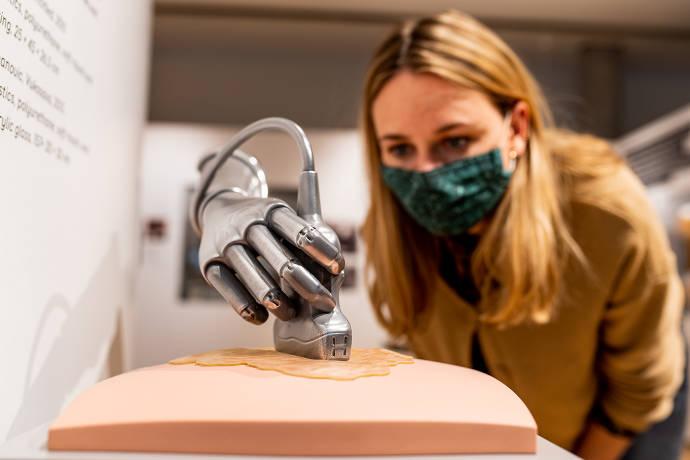 Frau mit Mundschutz betrachtet Kunstobjekt