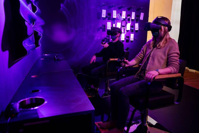 Sitzende Personen schauen sich über VR Kunsobjekte an