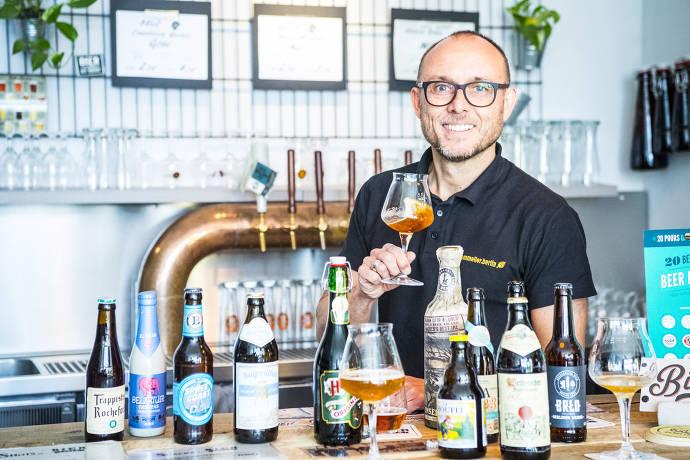 Mann hinter Bierflaschen, hält Glas in der Hand