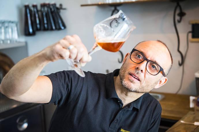 Mann, der Bierglas hält und betrachtet