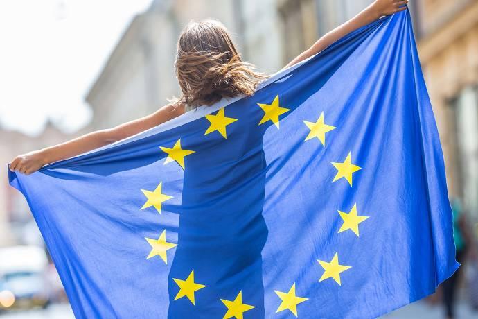 Frau steht mit dem Rücken zur Kamera und hält Europa-Flagge