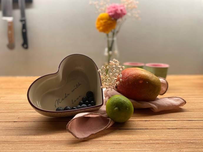 Herzförmige Schale mit Blaubeeren, Limette, Mango