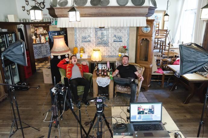 Zwei Männer sitzen in einem Wohnzimmer, Bier steht auf dem Tisch