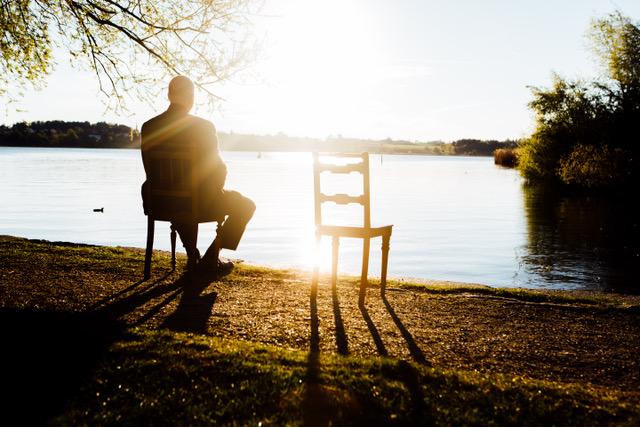 Mann sitzt allein auf einem Stuhl vor einem See