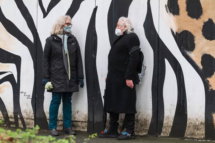 Zwei Personen vor einer Mauer mit Zebra-Muster