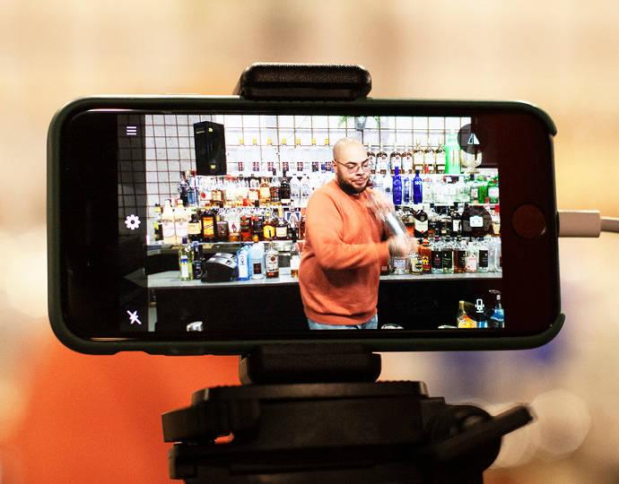 Barkeeper mixt Cocktail und wird mit einem Handy gefilmt