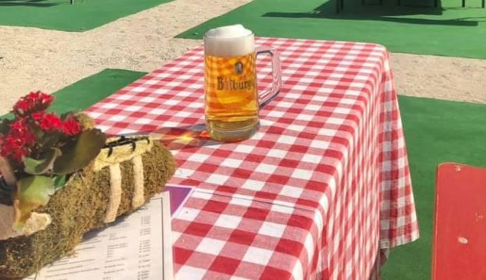 Biergarten, Tische stehen mit Abstand, frisch gezapftes Bier steh auf einem Tisch