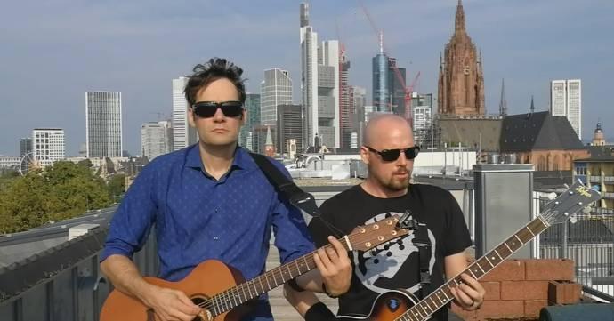 Zwei Männer mit Sonnenbrillen und Gitarren stehen auf einem Dach