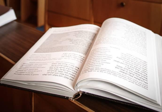 Offenes Buch liegt auf einer Holzbank