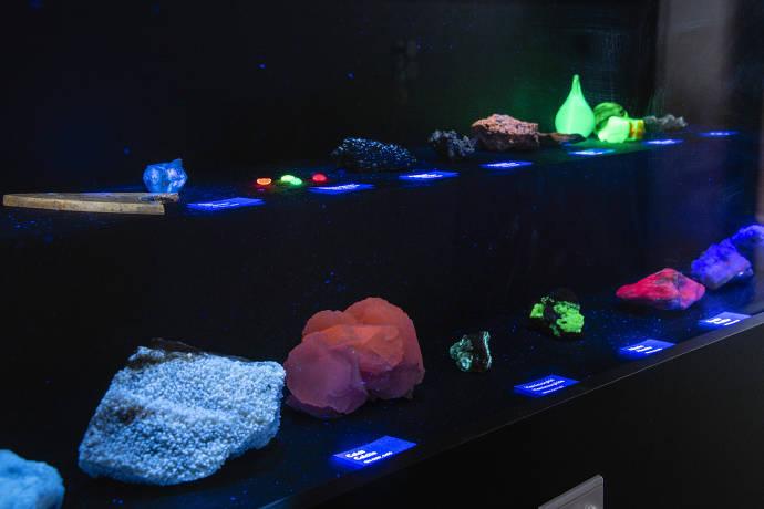 Fluoreszierende Minerale im Museum Wiesbaden. Werden Mineralen mit UV-Licht bestrahlt, leuchten einige von ihnen in mehr oder weniger hellen Farben auf. Dieser Effekt konnte erstmals am Mineral Fluorit gezeigt werden und wird daher als Fluoreszenz bezeich