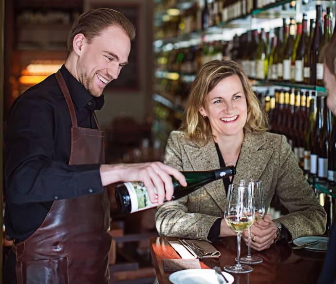 Ein Mann mit einer Schürze schenkt einer Frau Wein ein