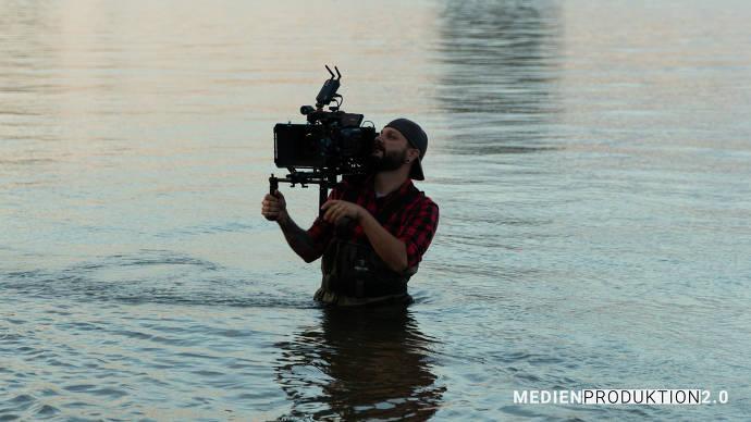 Mann steht mit Filmkamera im Wasser