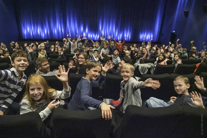 Kinder sitzen im Kino und winken in die Kamera
