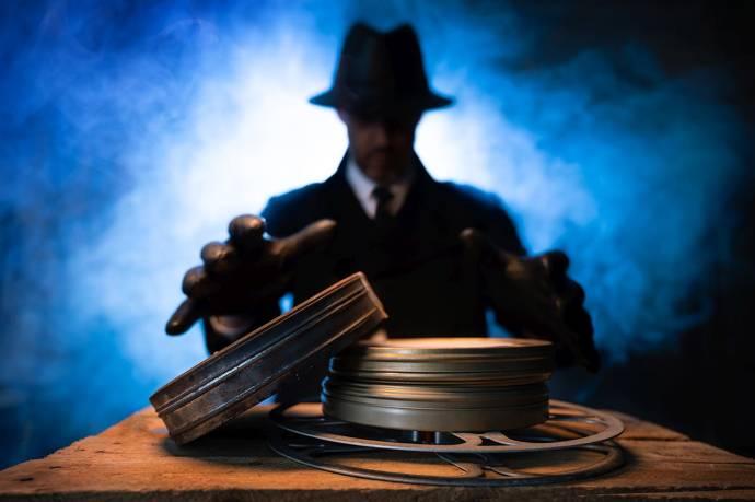 Ein Mann im schwarzen Anzug mit Handschuhen und Hut streckt die Hände nach Filmrollen aus
