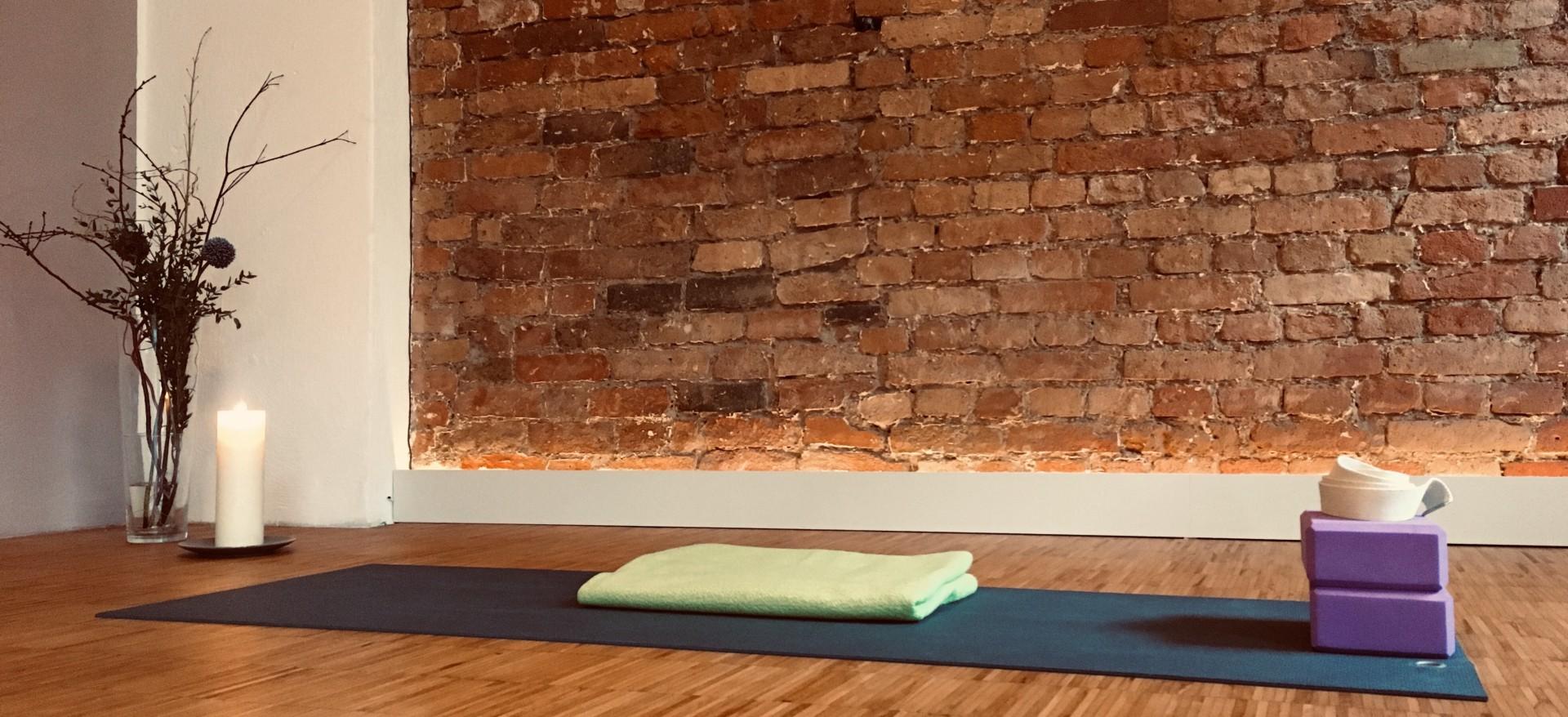Raumecke mit Backsteinwand, großer Blumenvase und Kerze. Im Vordergrund liegt eine Yogamatte und eine Decke.