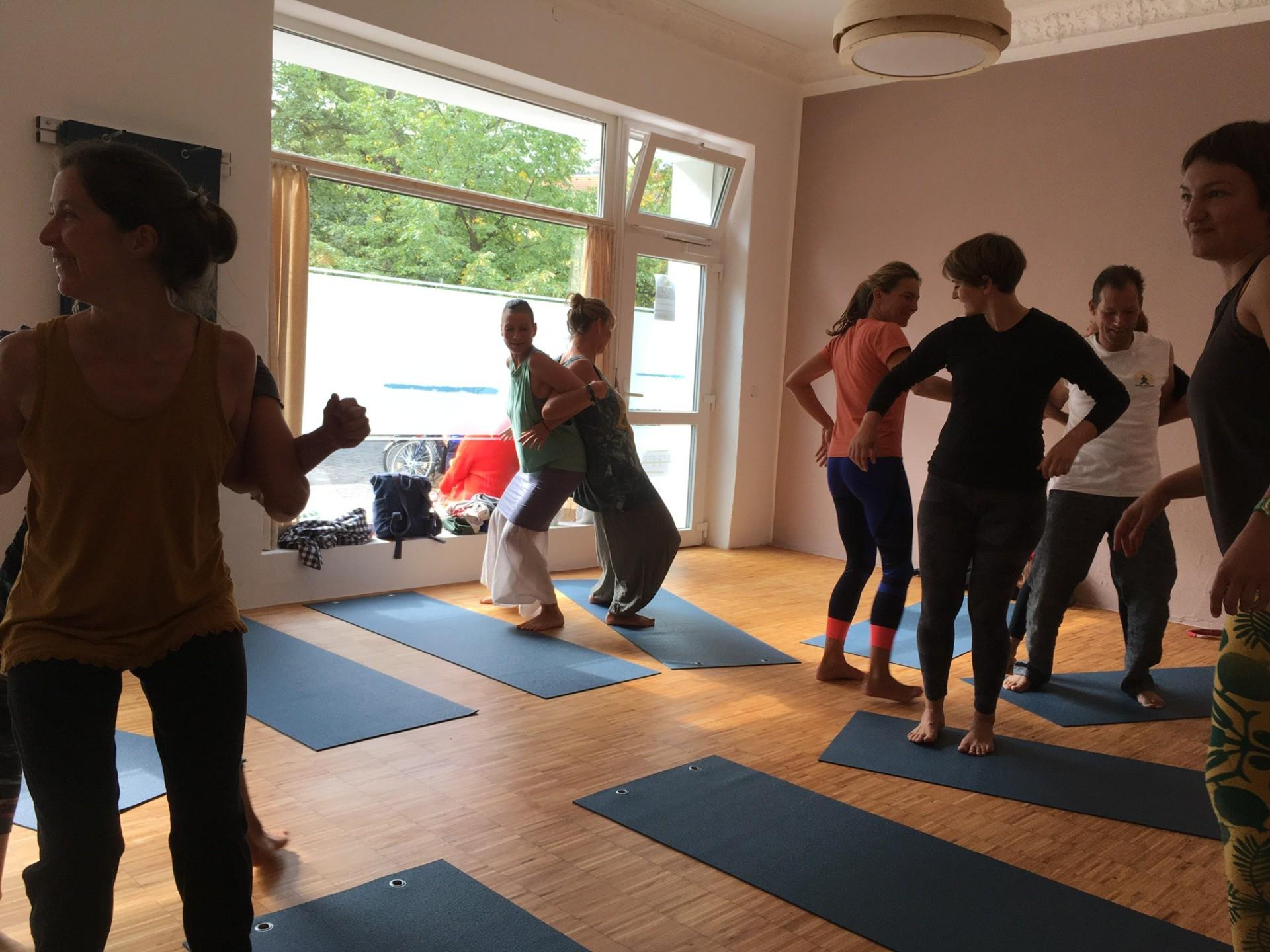 Raum mit großen Fenstern und sieben Frauen, die paarweise Yogaübungen machen.