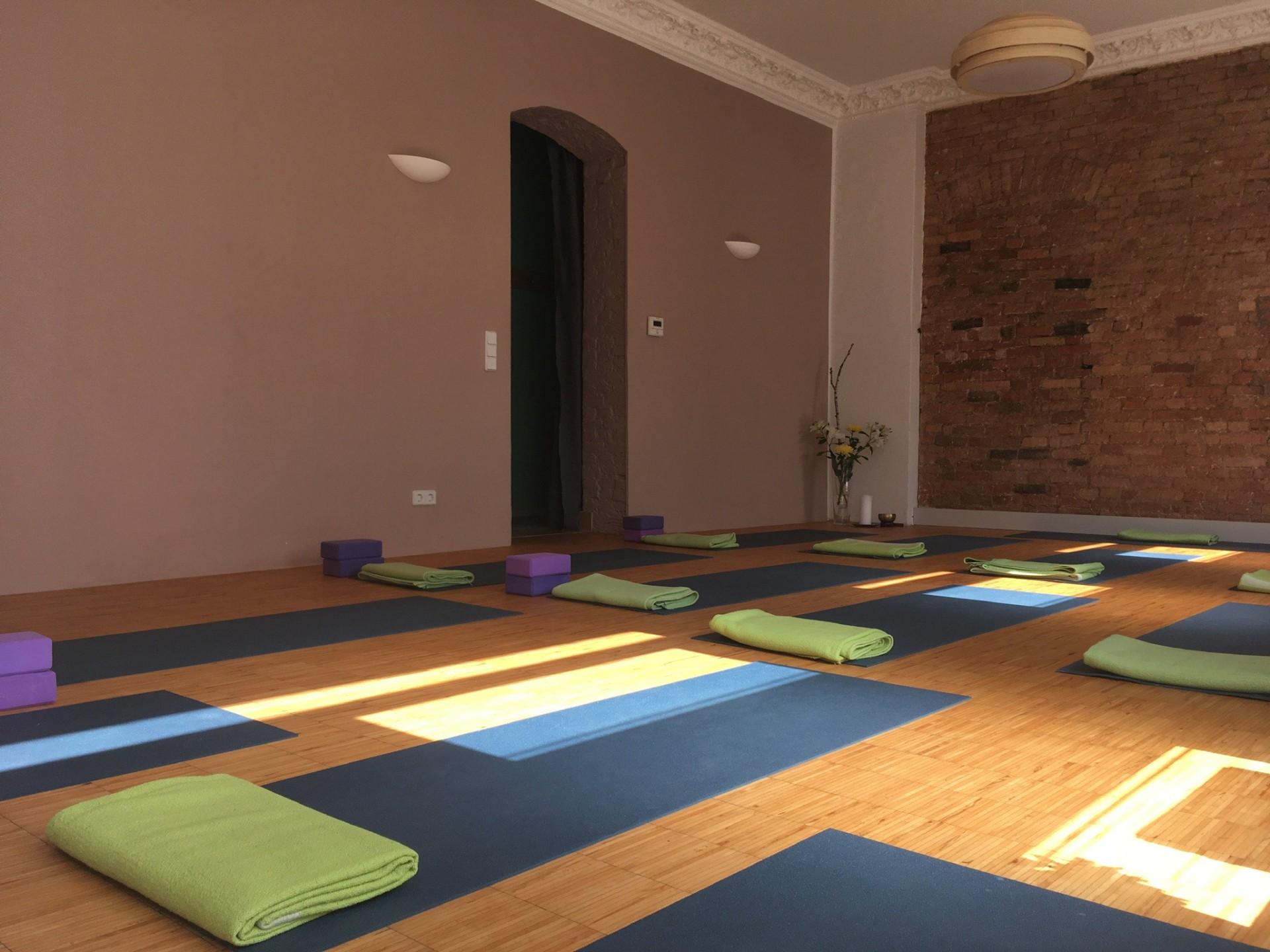 Großer Raum mit Backsteinwand und vielen yogamatten mit bunten Decken.