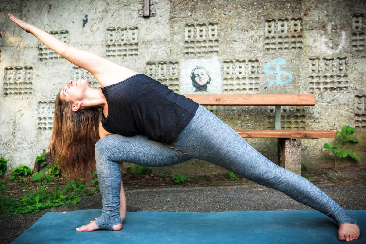 Frau in einer Yogastellung im Freien.