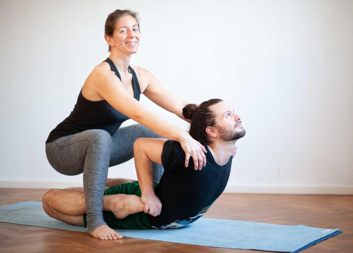 Lächelnde Frau hilft Mann mit Yogaübung.