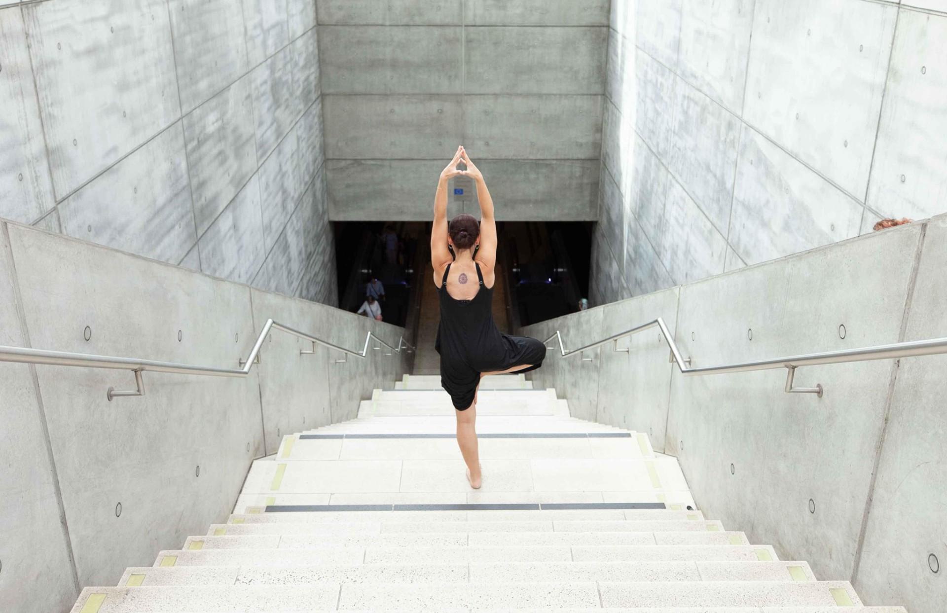 Frau in Yogapose auf einer Betontreppe.