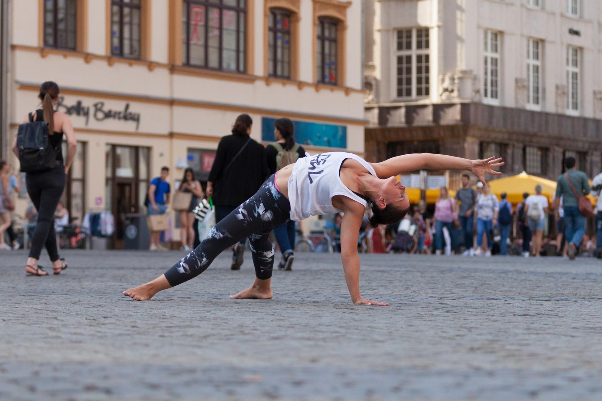 Frau in Yogapose auf einem Marktplatz.