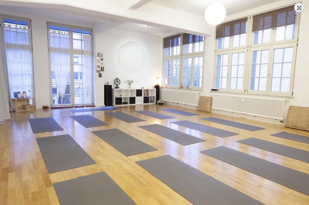 Großer, heller Raum mit großen Fenstern und vielen Yogamatten.