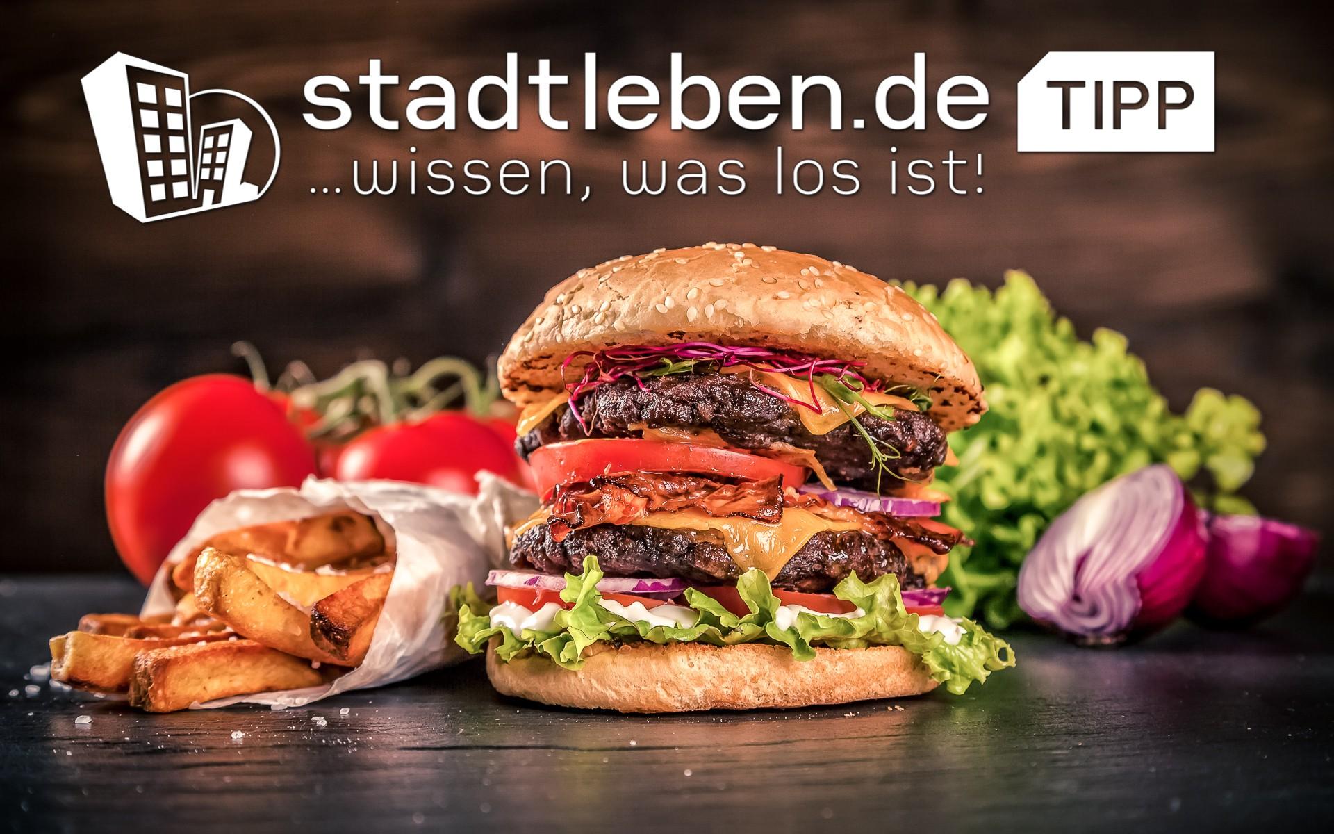 Leckerer Burger mit Rindfleisch, frischen Tomaten, Salat, Zwiebeln und Käse, dazu Pommes Frittes