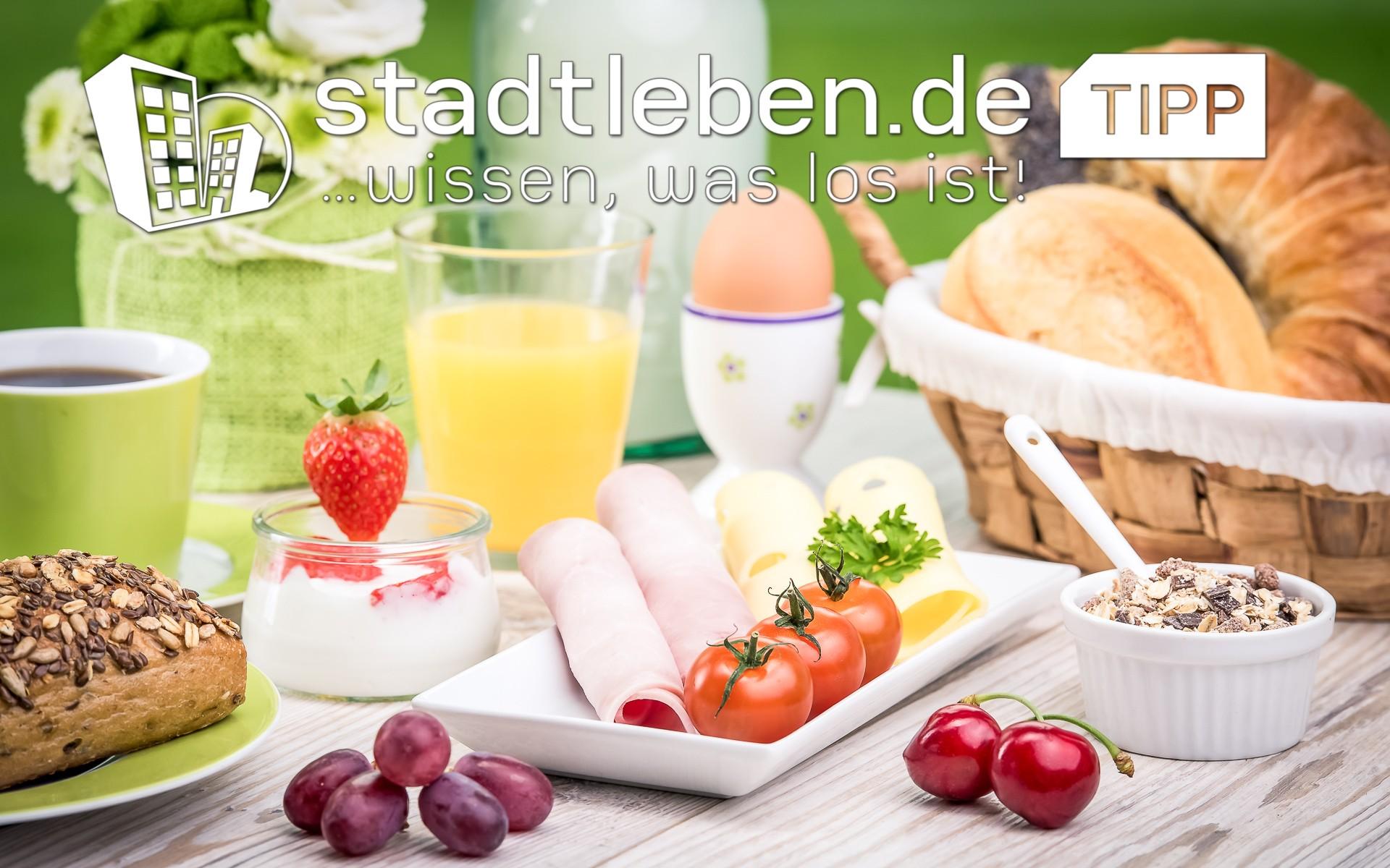Frühstück mit Körnerbrötchen, Müsli, frischem Obst, Tomaten, Käse, Ei, frischem O-Saft und Kaffee
