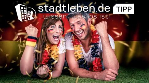Zwei Partner die Deutschland Trikot an haben und Jubeln, Deutschlandflagge