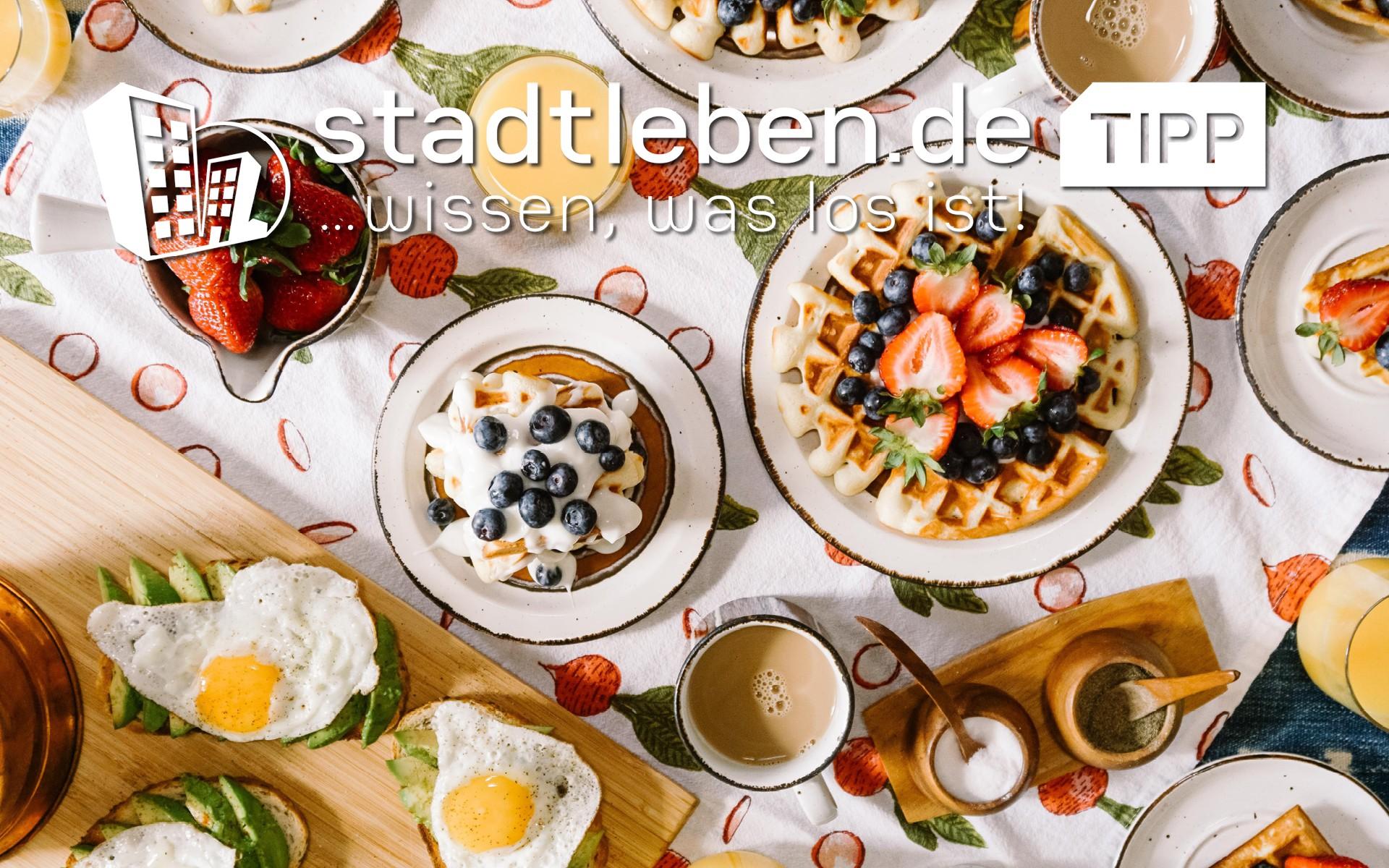 Frühstück mit Brötchen, Croissants, O-Saft, Orangen, Melone, Marmelade