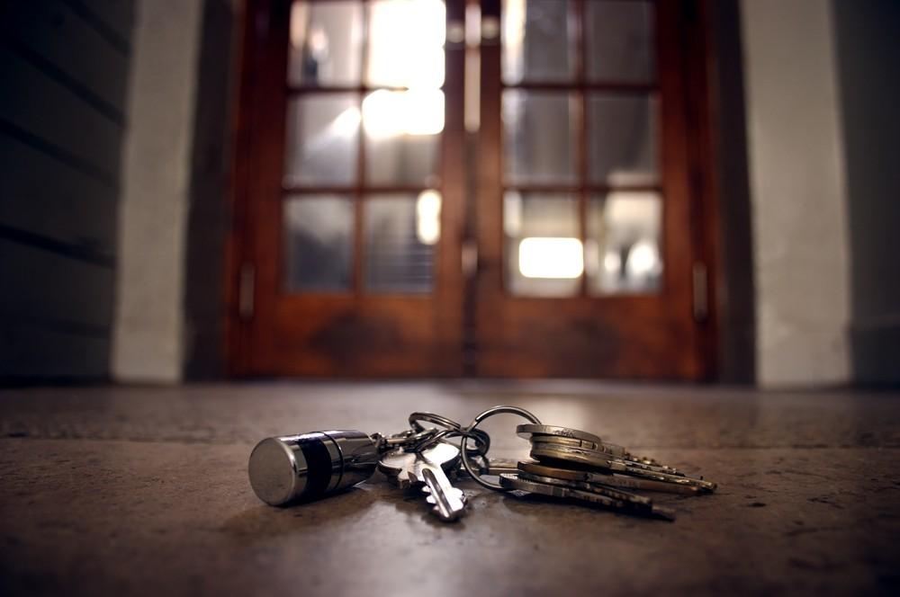 erlorener Schlüssel liegt vor einer verschlossenen Tür