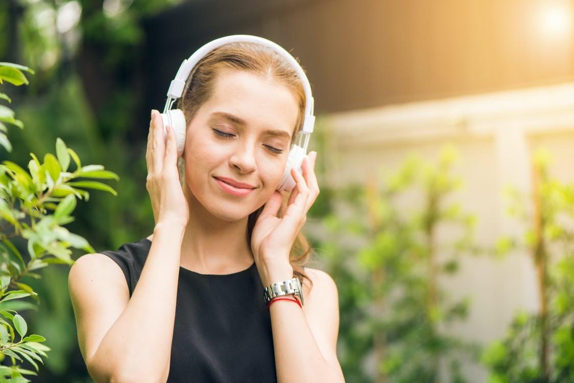 Frau, die schwarzes, ärmelloses Shirt trägt und über weiße Kopfhörer hört.