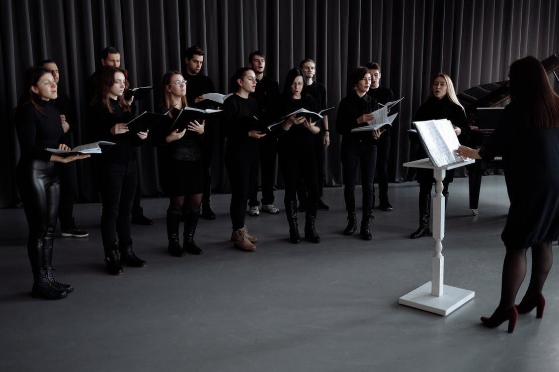 Gruppe von Menschen, die auf einer Bühne stehen, Chor, Dirigentin