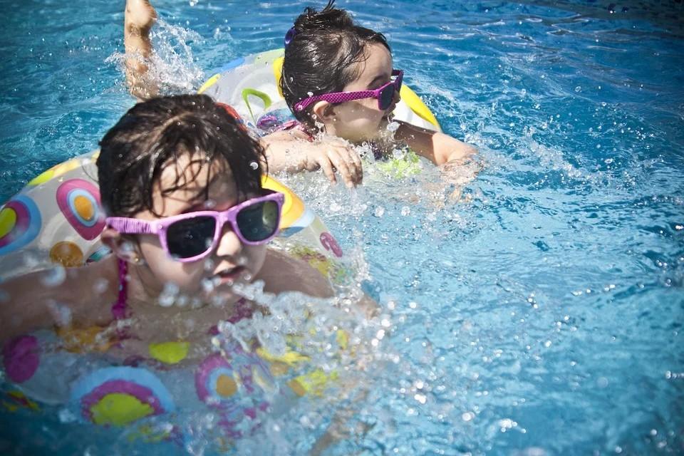 Zwei kleine Mädchen plantschen im Pool