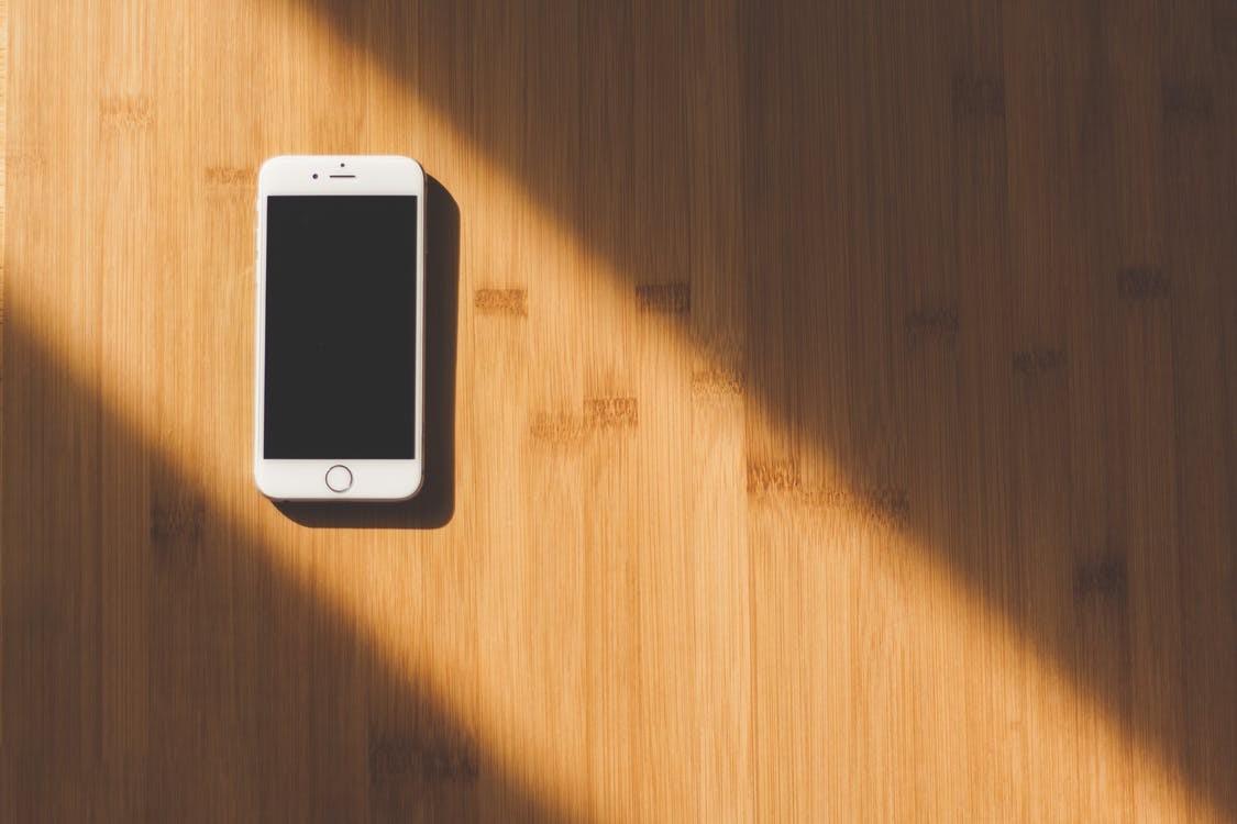 Ein weißes iPhone liegt auf einem Holztisch