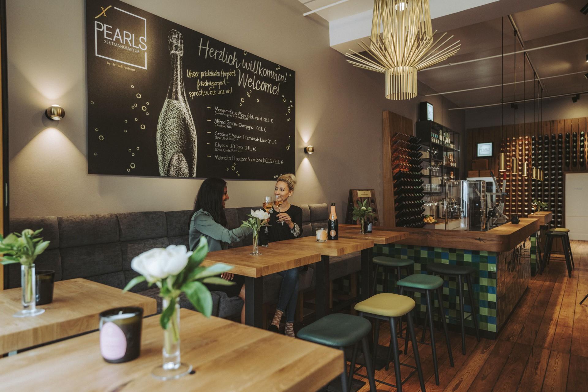 Zwei Frauen sitzen in der Weinbar und stoßen mit einem Glas Wein an