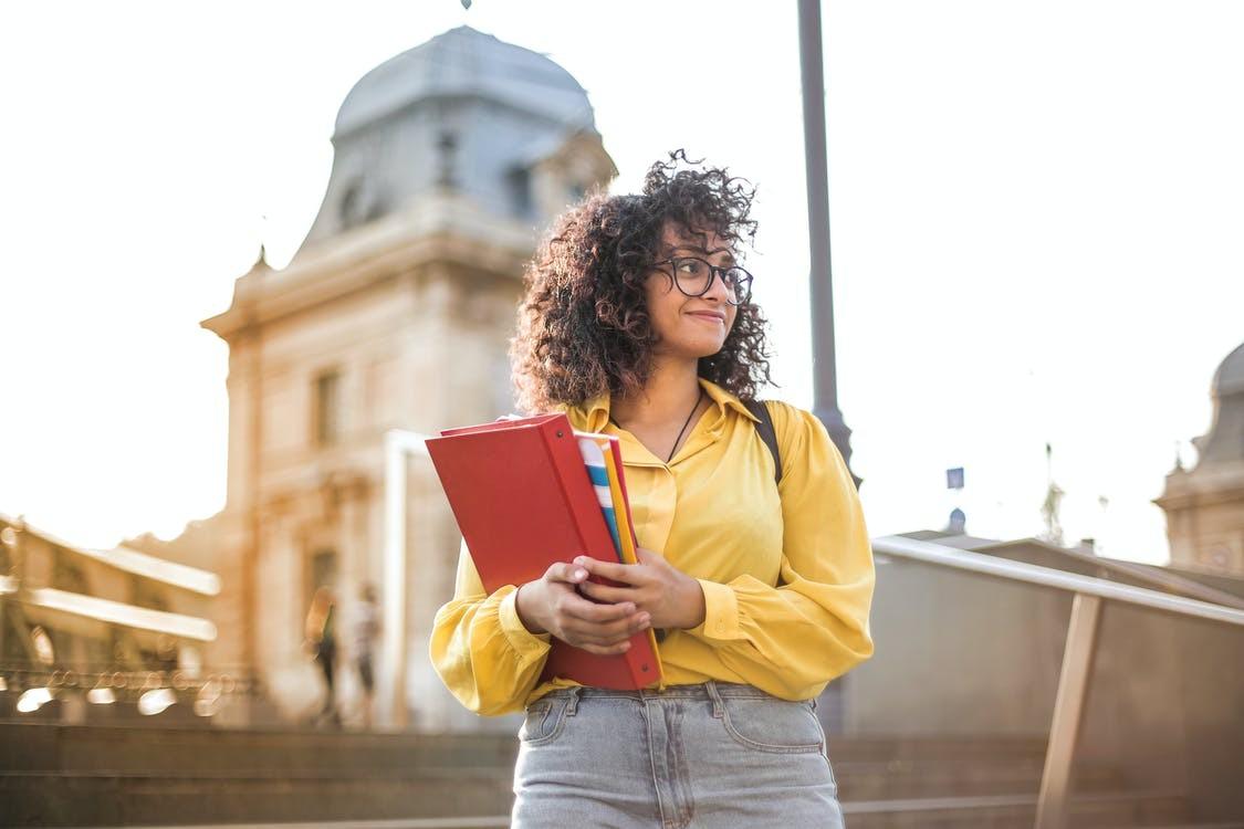 Frau in einer gelben Bluse, die einen roten Ordner hält