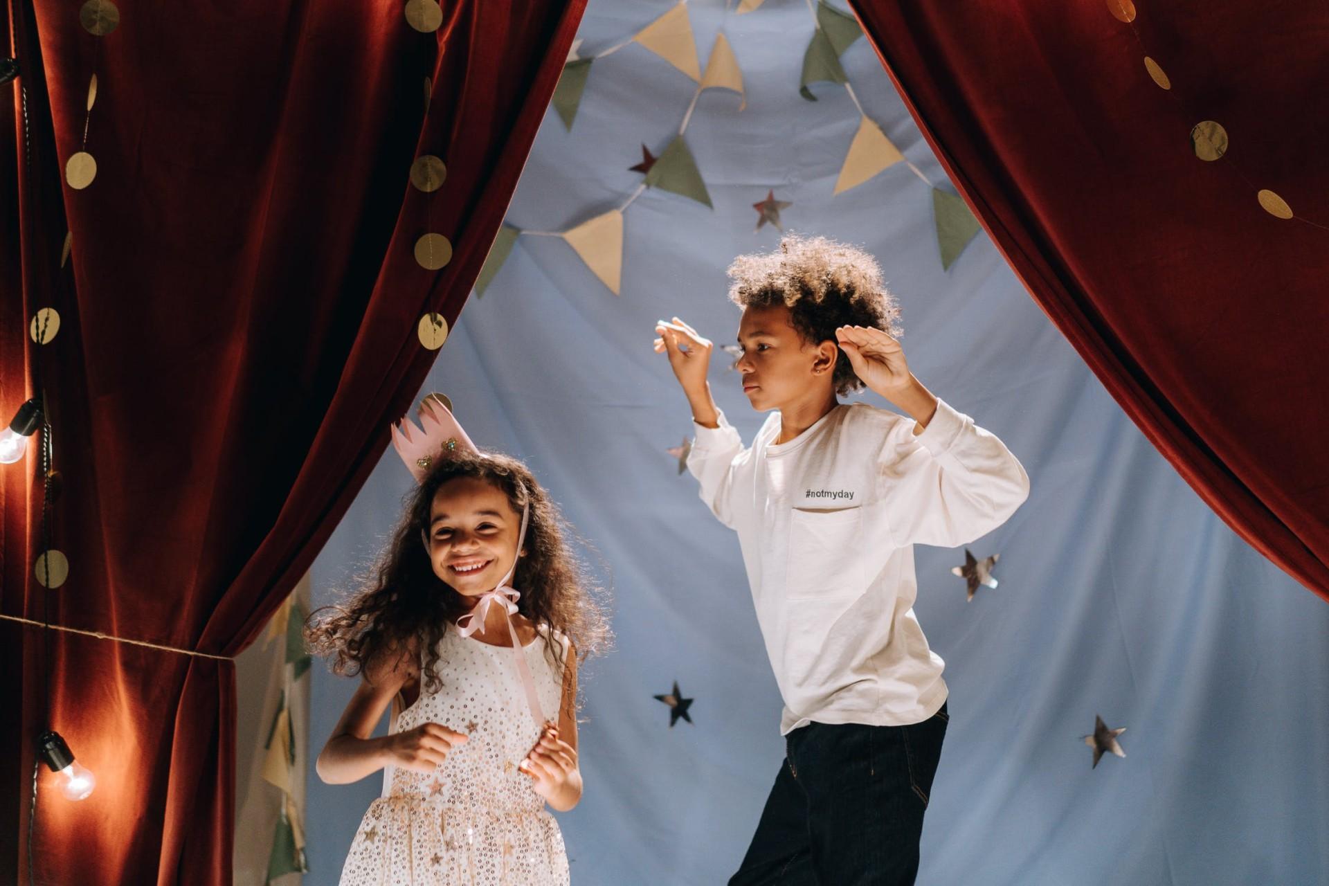 Junge und Mädchen stehen auf einer dekorierten Bühne