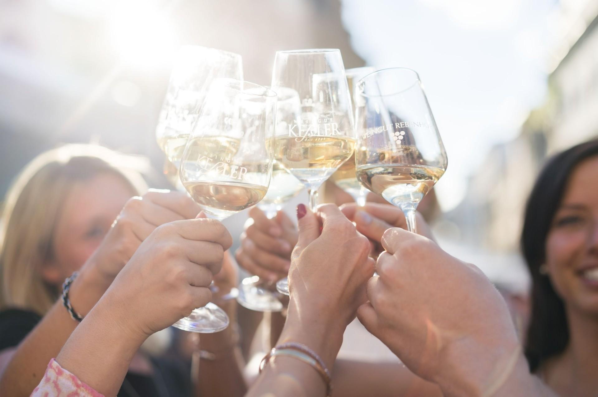 Eine Gruppe Menschen hält Weingläser in die Luft zum Anstoßen