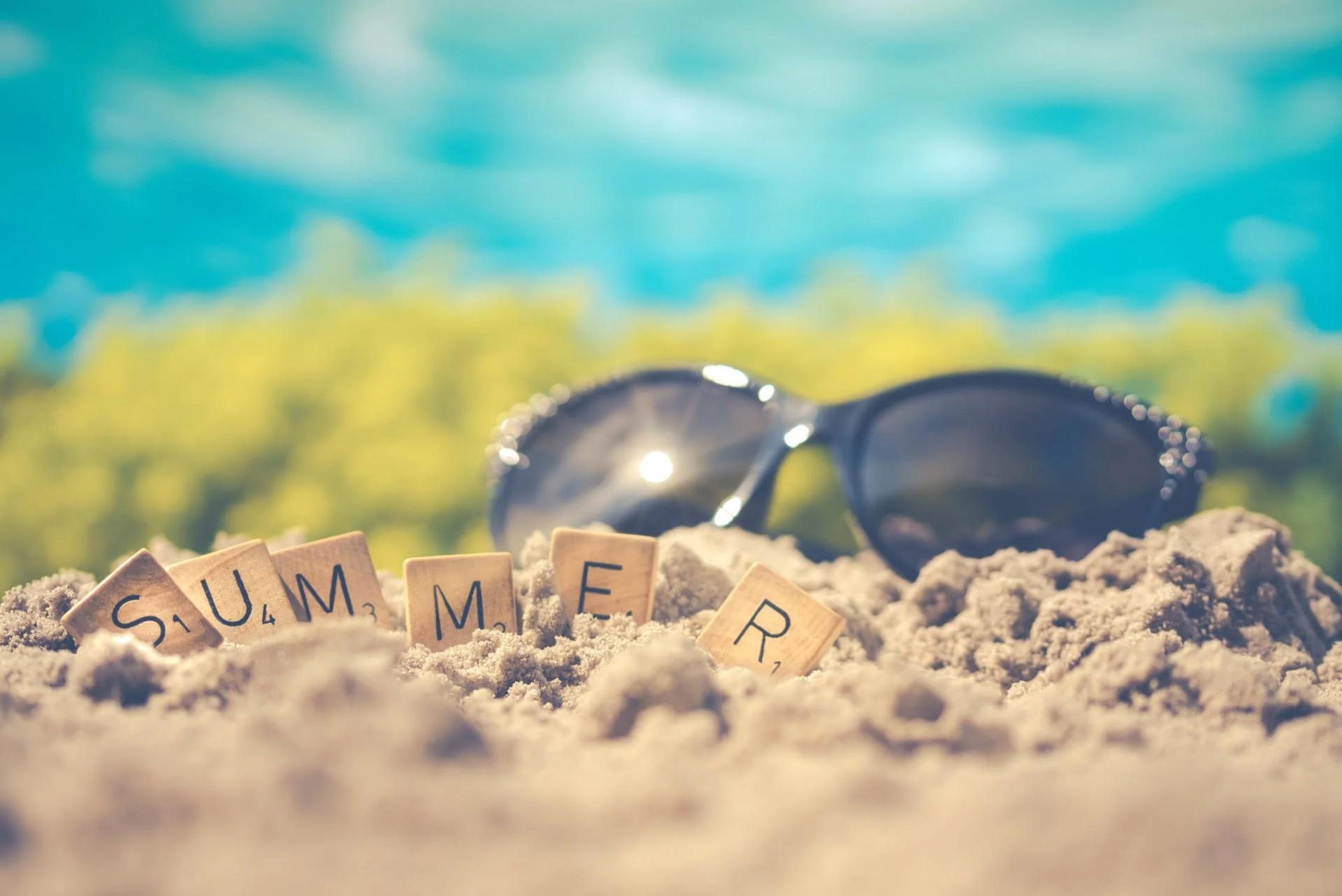 Eine schwarze Sonnenbrille liegt im Sand
