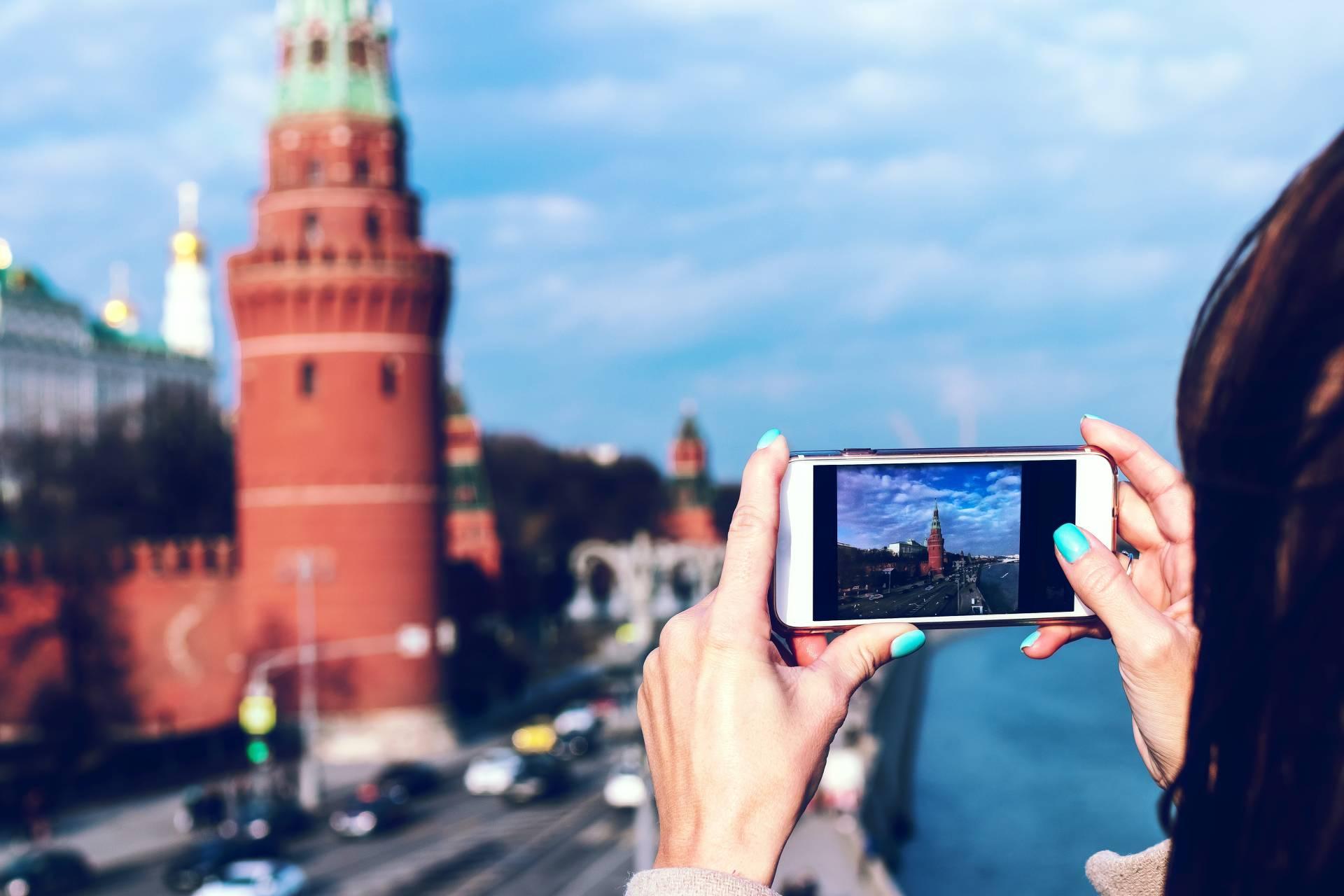 Frau fotografiert Gebäude mit Handykamera