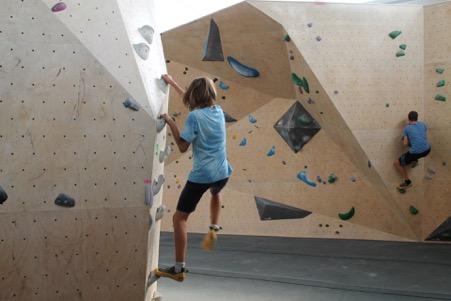 Kind klettert an Indoor Kletterwand