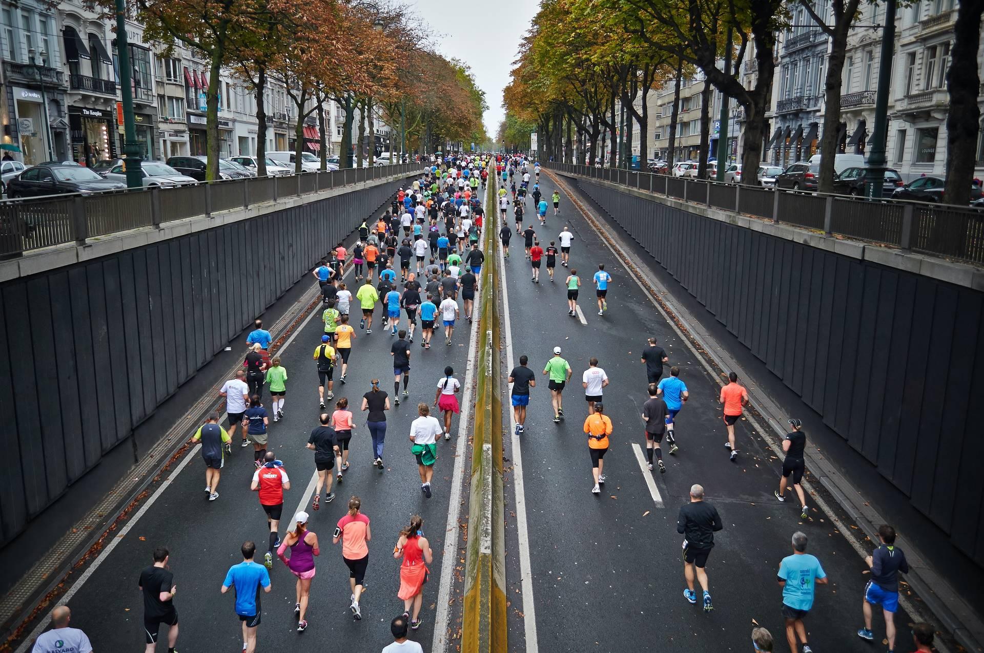 Jogger rennen auf Straße mit vielen bunten T-Shirts
