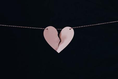 gebrochenes Herz aus Papier vor schwarzer Wand