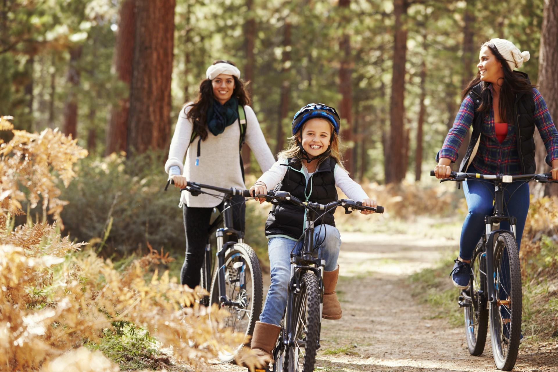 Zwei Frauen und ein Mädchen sind im Wlad mit Fahrrädern unterwegs