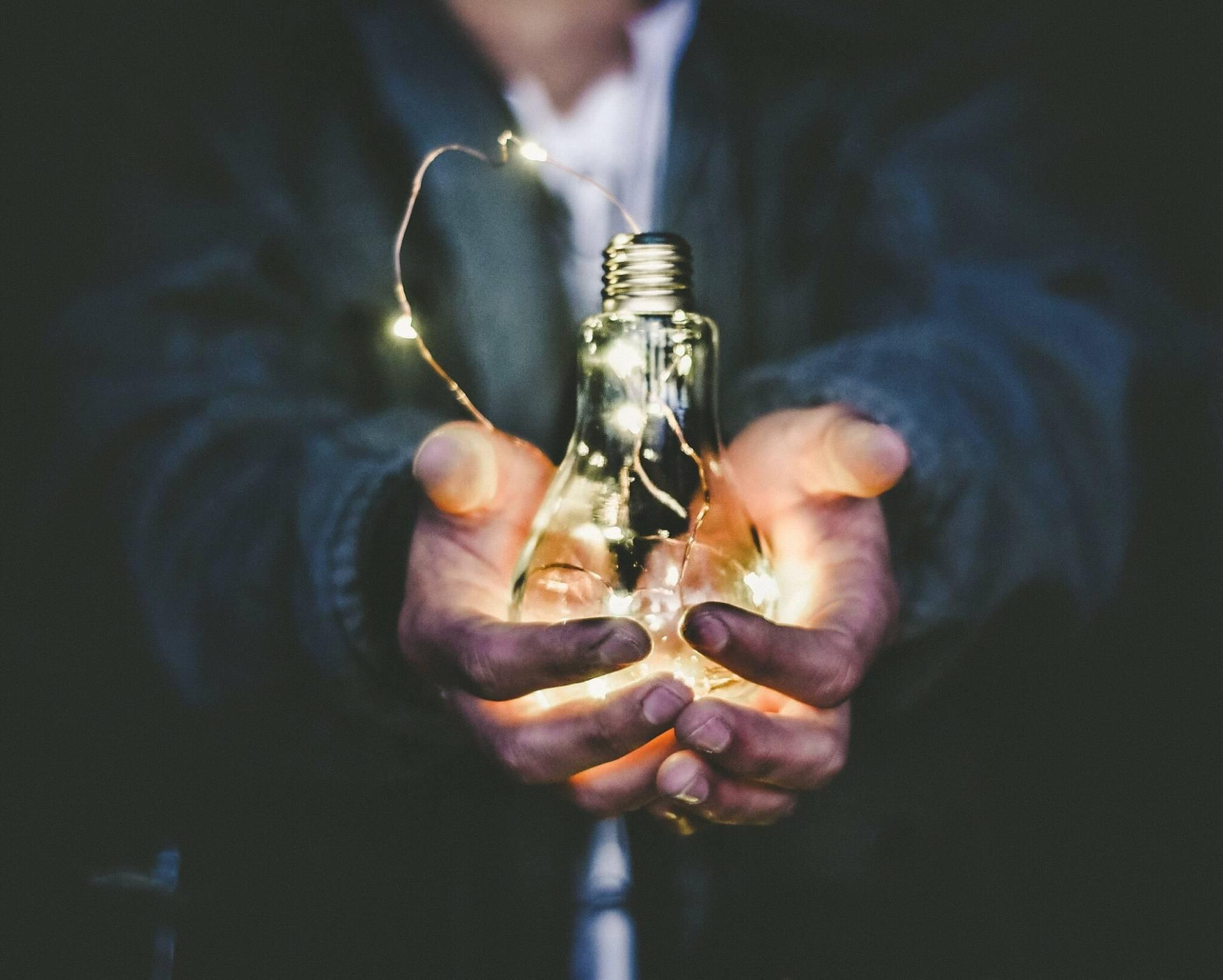 Mann hält leichtende Glühbirne in der Hand