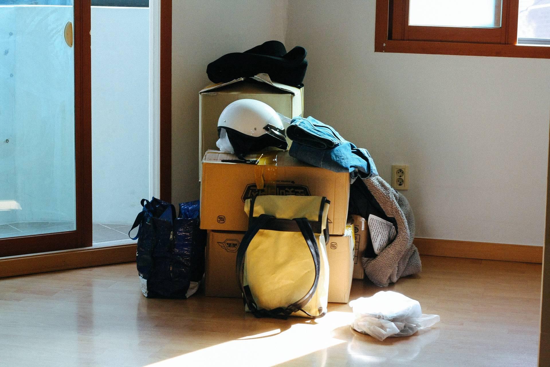 Umzugkartons mit Ruucksack und Kleidung stehend im Flur